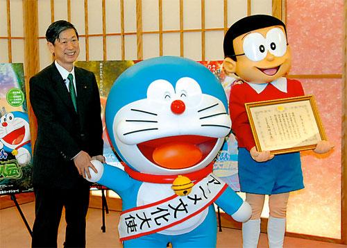 写真・外務省でアニメ文化大使就任式に臨むドラえもん(中央)と高村外務大臣... 外務省でアニメ文
